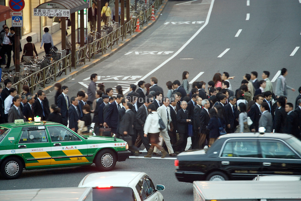 office worker crowd walking across a zebra crossing during rush hour