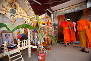 Donated items and money fill and adorn small funerary houses in the front of the family home in honor of Mr. Voua Sy Amkha, 63, a propaganda official for the Lao government in Luang Prabang, Laos, who died of a stroke. His funeral was held over a series of days—first at home with family and monks in Ban Navieng Kham village, a suburb of Luang Prabang, then cremation at the central crematorium site in Ban Vieng Mai, and then again at home a few days after the cremation ceremony.