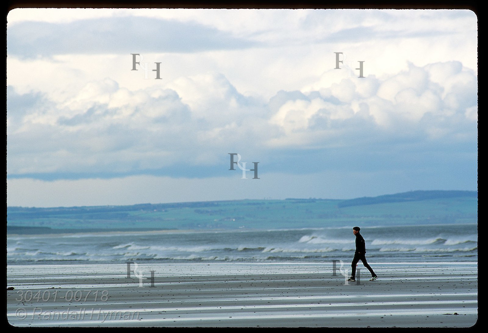 Man in black walks along beach on an April day in St. Andrews.  Scotland