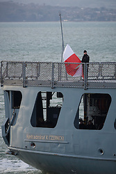 "© Licensed to London News Pictures. 09/01/2017. Portsmouth, UK.  A sailor raises the Polish flag on the stern of the Polish Navy's youngest ship, ORP Kontradmiral Xawery Czernicki, ""Czernicki"", as she sails into Portsmouth Harbour under Police escort this morning, 9th January 2017. The multi-role support ship is visiting Portsmouth before deploying on a 6-month mission to join Standing NATO Maritime Group 2 (SNMG2) in the Mediterranean Sea. Photo credit: Rob Arnold/LNP"