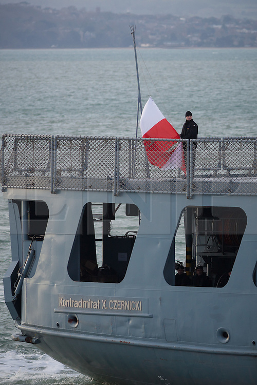 """© Licensed to London News Pictures. 09/01/2017. Portsmouth, UK.  A sailor raises the Polish flag on the stern of the Polish Navy's youngest ship, ORP Kontradmiral Xawery Czernicki, """"Czernicki"""", as she sails into Portsmouth Harbour under Police escort this morning, 9th January 2017. The multi-role support ship is visiting Portsmouth before deploying on a 6-month mission to join Standing NATO Maritime Group 2 (SNMG2) in the Mediterranean Sea. Photo credit: Rob Arnold/LNP"""