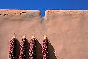 Large chili rostras on adobe wall at the entrance to the Martinez Hacienda (circa 1804), Taos, New Mexico
