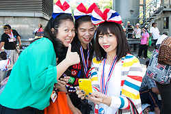 © Licensed to London News Pictures. 05/01/2014. Protestors wearing headpieces in the Thailand national colours pose gather around an smart phone for a group photo during the third day of the 'Bangkok Shutdown' as anti-government protesters continue with their 'shutdown' of Bangkok.  Major intersections in the heart of the city have been blocked in their campaign to oust Prime Minister Yingluck Shinawatra and her government in Bangkok, Thailand. Photo credit : Asanka Brendon Ratnayake/LNP