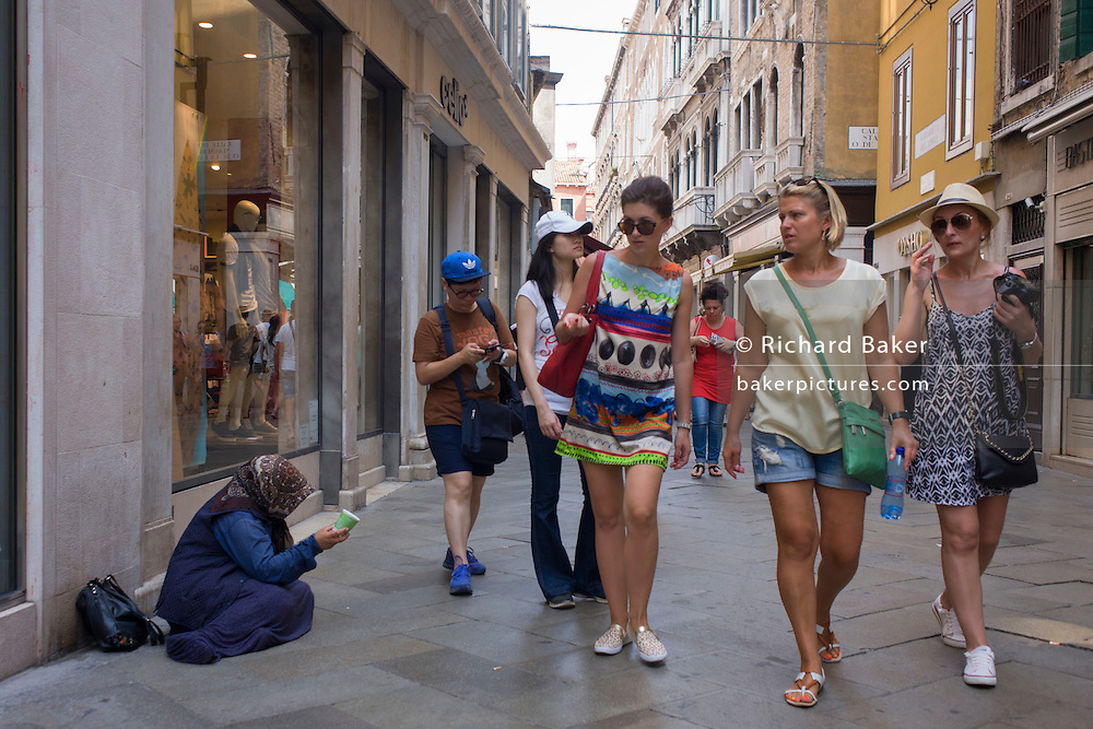 Women tourists walk past a female street beggar in the San Marco shopping district of Venice, Italy.