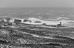 Heavy storm and surf at the coastline in Grimsey, north of Iceland.  The homes and the church are vulnerable compared to mother nature - Stormur og öldur við ströndina  í Grímsey, hús og byggingar eru smáar í samanburði