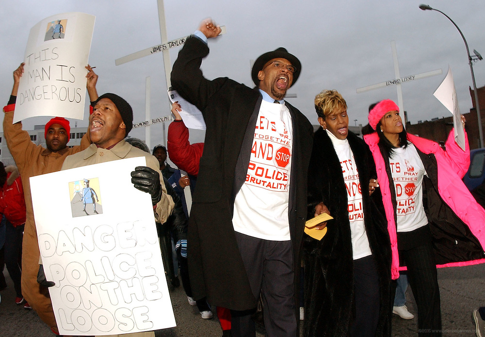 """Chanting """"public lynching,"""", Jerry Bouggess, his wife Angela, Toni Mitchell and her son Jeff, lead a protest Thursday, Jan. 8, 2004, through downtown Louisville, Ky., of the shooting of his stepson Michael Newby by a white police officer. (AP Photo/Brian Bohannon)"""