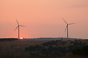 two Electric Generator, Wind turbine, between Buccheri and Palazzolo on the Iblei mountains, province of Siracusa, Sicily, Italy, at sun set July 2006