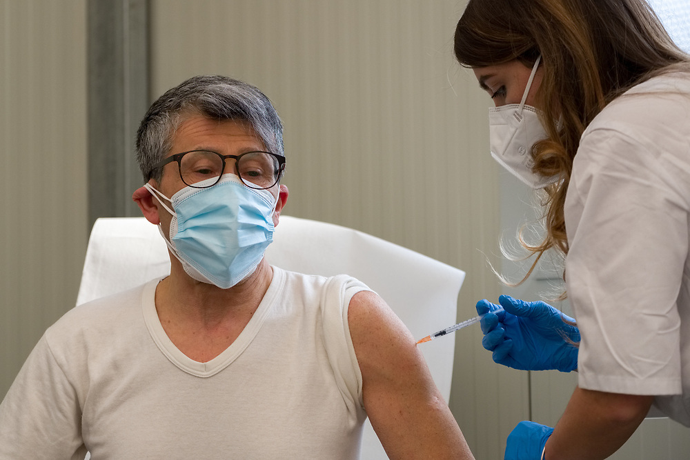 """A man receives a dose of the AstraZeneca COVID-19 vaccine in the Covid Vaccine Center on March 4, 2021 set up in the """"Ferrari-Orsi"""" barracks of the Brigata Bersaglieri Garibaldi (Bersaglieri Garibaldi Brigade) in Caserta, southern Italy, as part of vaccinations for teachers and school staff. The center is the largest in the Campania region, with 26 stations where up to three thousand vaccines can be administered per day."""