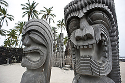 """Ki'i (wooden images) stand guard over a reconstruction of a hawaiian temple and mausoleum of early Hawaiian royalty at Pu'uhonua o Honaunau National Historic Park on the Big Island of Hawaii. Early Hawaiians who broke a law (kapu) could avoid death by fleeing to Pu'uhonua o Honaunau where they would be absolved by a priest. Because of this, Pu'uhonua o Honaunau is sometimes referred to as the """"City of Refuge."""""""