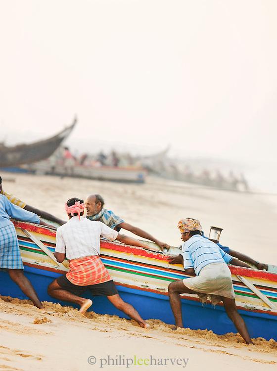 Fishermen bring their boat back to shore at Poovar Beach, near Trivandrum (Thiruvananthapuram), Kerala, India