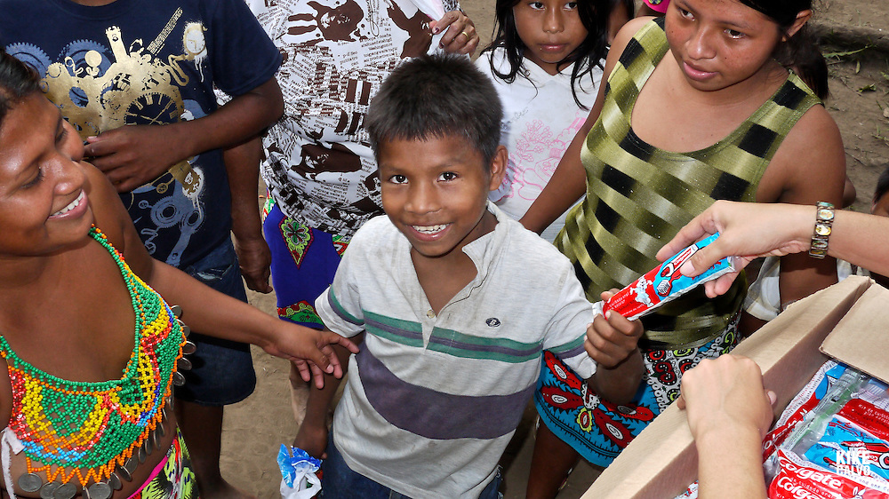 Over the last quarter-century, a few Embera families pushed further North of Darien, settling in the jungles bordering the Ipeti? River -- a scant two-hour journey from cosmopolitan Panama City. Embera communities are scattered in this border wilderness. Pictured: Children receiving tooth brush and past.