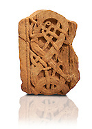Anglo Saxon sandstone cross shaft fragment, 775-840. The complicated pattern depicts ribbon shaped animals with long thin bodies and legs. An animals face can be seen in the bottom right in profile with one eye and a mouth .Lindisfarne Abbey Museum, Northumbria, England