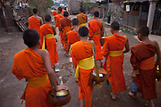 "Ban Saylom Village, just South of Luang Prabang, Laos. Every morning at dawn, barefoot Buddhist monks and novices in orange robes walk down the streets collecting food alms from devout, kneeling Buddhists. They then return to their temples (also known as ""wats"") and eat together. This procession is called Tak Bat, or Making Merit."