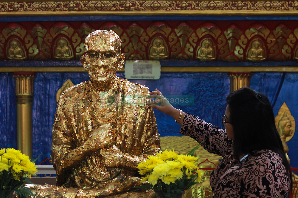 May 10, 2017 - Penang, Malaysia - A devotee put a golden paper  onto  Buddha statue during Vesak day in Penang, Malaysia, on May 10,2017. Buddhists around the world have celebrate Vesak ,one of the most important day in Buddhist calendar informally known as Buddha 's birthday, it commemorates the birth, enlightenment and the death of Buddha, Siddhartha Gautama.Buddhist scriptures state that each occurred on the full moon of the Indian lunar month of Vesakha.Buddhists celebrate Vesak every year on the day of full moon in May. (Credit Image: © Shaiful Azre/NurPhoto via ZUMA Press)