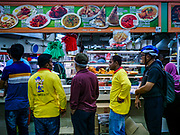 "11 DECEMBER 2018 - SINGAPORE: People lined up a food shop in a ""hawker court"" in the Geylang neighborhood. Singapore forced food venders off the street and put them in hawker courts years ago. The Geylang area of Singapore, between the Central Business District and Changi Airport, was originally coconut plantations and Malay villages. During Singapore's boom the coconut plantations and other farms were pushed out and now the area is a working class community of Malay, Indian and Chinese people. In the 2000s, developers started gentrifying Geylang and new housing estate developments were built.    PHOTO BY JACK KURTZ"