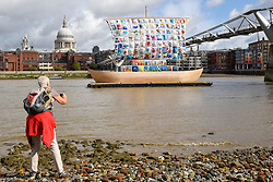 """© Licensed to London News Pictures. 04/09/2019. LONDON, UK. A tourist takes a photo during the photocall for the launch of """"The Ship of Tolerance"""" at Tate Modern, Bankside.  The floating installation by Emilia Kabakov (of Russian conceptual artist duo Ilya and Emilia Kabakov) forms part of Totally Thames Festival and will be moored 4 September to 31 October.  The goal of the artwork is to educate and connect the youth of the world through the language of art.  Photo credit: Stephen Chung/LNP"""
