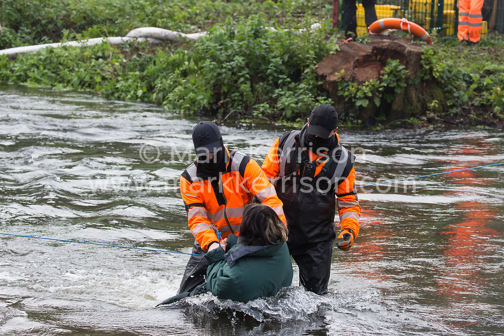 Denham, UK. 5th November, 2020. A HS2 security guard restrains a female anti-HS2 activist in the river Colne at Denham Ford during bridge building works for the HS2 high-speed rail link on the first day of the second national coronavirus lockdown. Prime Minister Boris Johnson has advised that construction work may continue during the second lockdown but those working on construction projects are required to adhere to Site Operating Procedures including social distancing guidelines to help prevent the spread of COVID-19.