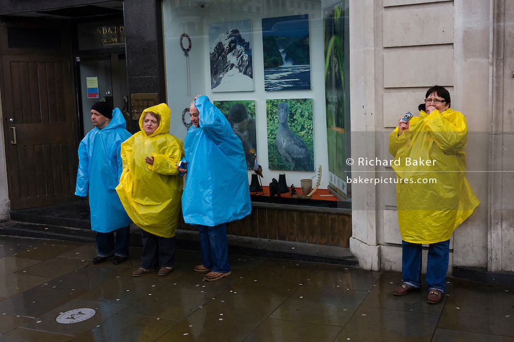 Similarly-dressed tourist couples tour London in the rain, stopping to take take in the sights of the UK capital.