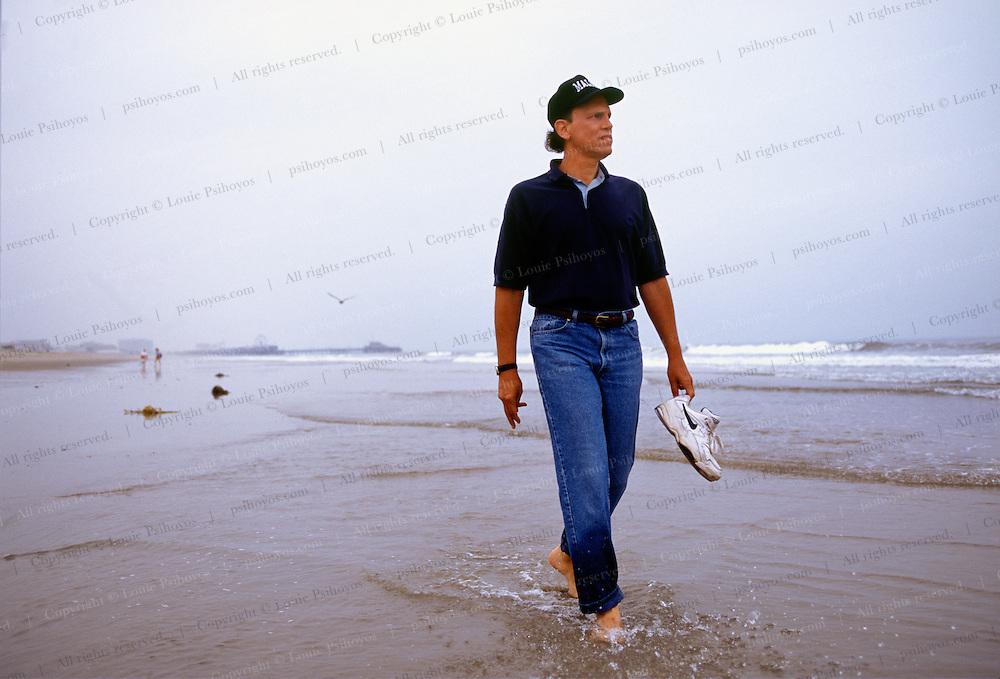 Michael Milken is a philanthropists pioneering financier of junk bonds and an inside trader.  Walking on the beach near his office in Santa Monica.