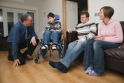 Professional visiting family with boy with cytomegalovirus syndrome at home.