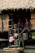 Mother and children at their traditional wood and straw roofed home in the Solomon Isles.