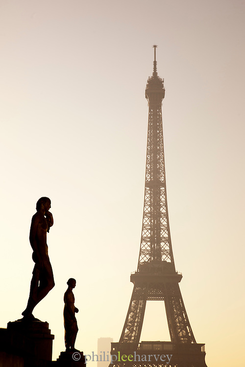 The silhouettes of statues at the Trocadero, before the iconic Eiffel Tower in Paris, France