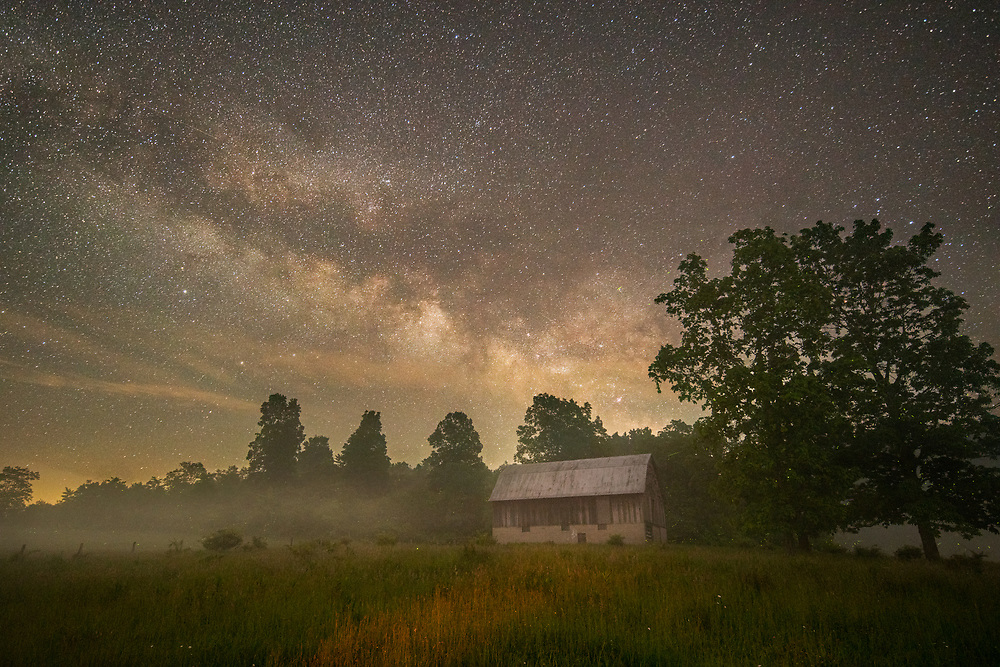 Fireflies dot the fields around a barn under the great Milky Way as a fog begins to lift from the surrounding countryside in Randolph County, West Virginia.