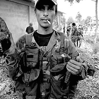 An AUC paramilitary fighter holds up a homemade 'Claymore' anti personnel mine in a village near La Dorada, Putumayo.<br />