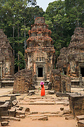 A woman in a red dress and bright pink hat stands in front of the central tower of the ancient Preah Ko temple, Roluos, Svay Chek District, Banteay Meanchey Province, Cambodia, South East Asia. <br /> The tower is made of brick and perches on a sandstone platform. This tower is dedicated to Jayavarman II, the founder of the Khmer empire.