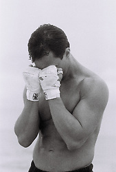 Young man wearing boxing bandages and covering his face