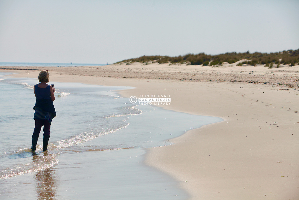 Covid 19 - A lone woman records the usually packed beach owned by the National Trust at Shell Bay Dorset. Normally very busy with visitors now empty and closed due to coronavirus. UK April 2020. MR