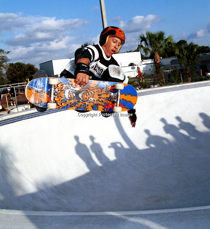 """Tom Leggett, of Jupiter, completes a front side rock """"n"""" roll during a skateboard exhibition on Tuesday, March 16 1999 in West Palm Beach, Fla. Shadows of onlookers are cast in the background at the new Oelsner skate Park at the YMCA on Congress Ave.The park was officially dedicated Tuesday in honor of the late Warren """"Jimo"""" Oelsner,a community youth and in line skating supporter. (Photo by Steve Mitchell)"""