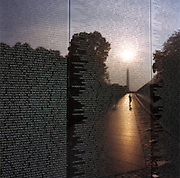 Vietnam memorial, Washington DC. Patriotic Americana - After 9/11. Vietnam memorial names and reflected visitor, Washington DC. In the week after the September 11th attacks, America sought to express their anger and patriotic unity. At dawn, a lone person pays their respects at the Vietnam Memorial wall in Washington DC...