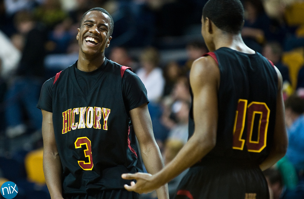 Hickory's Trez Shuford laughs with teammate Jalen Byrd late in the game against Concord during the regional round of the NCHSAA 3A playoffs Thursday night at the University of North Carolina at Greensboro. Hickory won the game 95-82 to end the Spiders season. (Photo by James Nix)