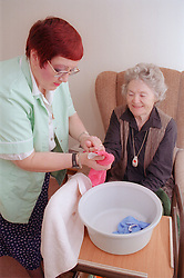 Carer assisting elderly woman by washing her hand,