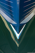 The detail of a blue boat bow is reflected in the water while at moorage in Winslow, Washington