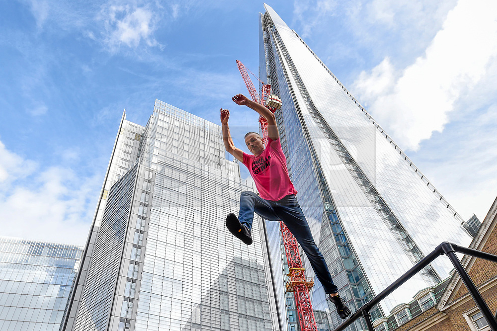 """© Licensed to London News Pictures. 10/10/2019. LONDON, UK. Alister O'Loughlin, a member of the Urban Playground Parkour Team, rehearses """"Zoo Humans"""" in the courtyard of Guy's Hospital adjacent to The Shard building to kick of the Dance Umbrella 2019 festival.  The show is inspired by the shocking statistic that three quarters of young people in the UK spend less time outdoors than prisoners.   Photo credit: Stephen Chung/LNP"""