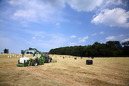 Wrapping big hay bales with tractor and trailer