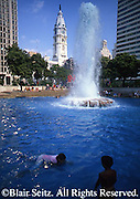 Young children bath in Ellen Phillips Samuel Memorial Fountain pool, City Hall in background, Love Park, John F. Kennedy Plaza, Philadelphia, PA