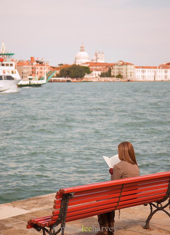 Woman reading alongside the Canale della Giudecca. Venice, Italy, Europe