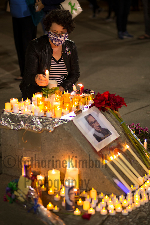 """KATIE PRYDE of Portland, OR, adds a candle to a memorial for Supreme Court Justice Ruth Bader Ginsburg during a candlelight vigil Saturday night. """"I'm a single mother and a business owner,"""" she said. """"The freedoms that I have to do the things I do came from RBG."""" After a brief pause she added, """"and I think I need to get my tubes tied!""""  Almost 300 people gathered in Portland Oregon on Saturday evening to mourn the death of Surpreme Court Justice Ruth Bader Ginsburg in an event titled, """"Ruthlessly Vigil, A Candlelight Memorial for RBG"""" on September 19, 2020 one day after Justice Ginsburg died. She was 87 years old."""