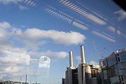 Seen from the window seat of a train carriage that is travelling towards Victoria station, is a landscape of cranes and gantries at the large Battersea Power Station construction site, in London, England, on 11th February 2020, in London, England.
