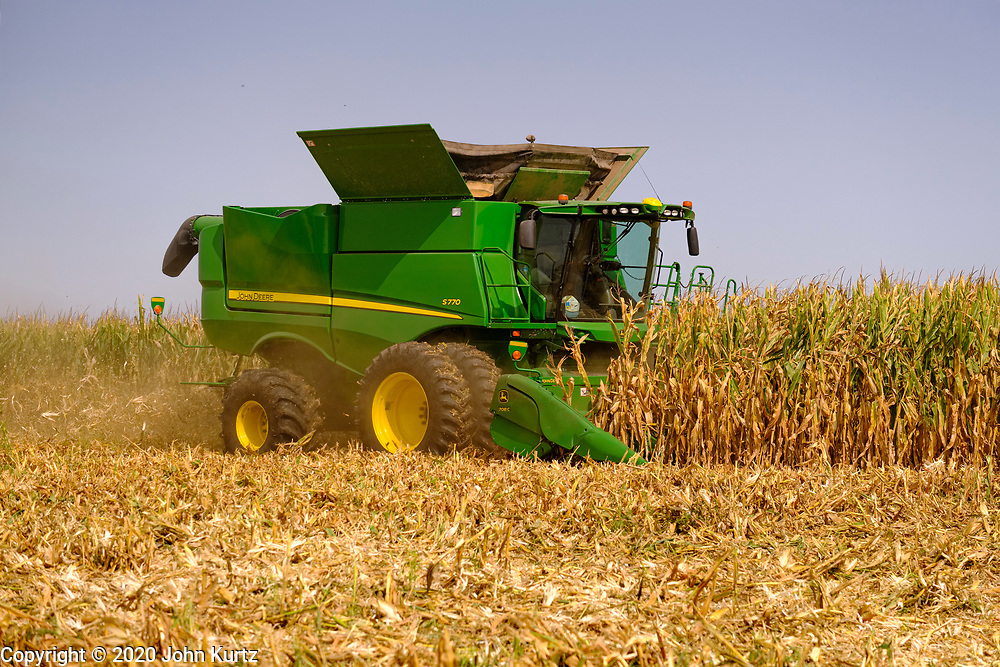 """14 SEPTEMBER 2020 - WINTERSET, IOWA: A farmer harvest corn in his field northeast of Winterset, in Madison County, Iowa. The US Department of Agriculture recently lowered its corn and soybean outlooks because of a persistent drought in Iowa and parts of the Midwest. """"August was a month of extreme weather and climate disasters,"""" USDA said in its monthly Crop Production report. """"There were also slow-motion events, such as worsening Western drought and a stripe across the Midwest and Northeast that experienced significant rainfall deficits."""" Iowa's harvest was also hurt by the derecho wind storm in August, although that storm didn't hit Winterset.     PHOTO BY JACK KURTZ"""