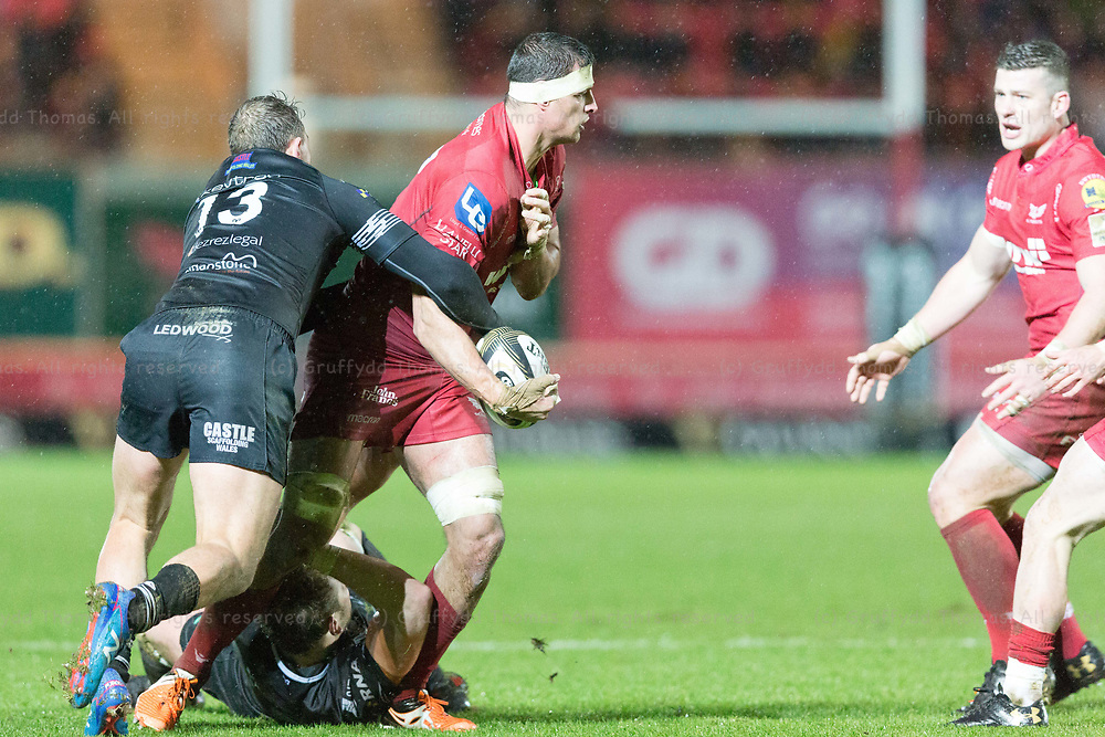 Parc y Scarlets, Llanelli, Wales, UK. Tuesday 26 December 2017.  Scarlets flanker Aaron Shingler offloads as Ospreys centre Kieron Fonotia makes a tackle in the Guinness Pro14 match between Scarlets and Ospreys.