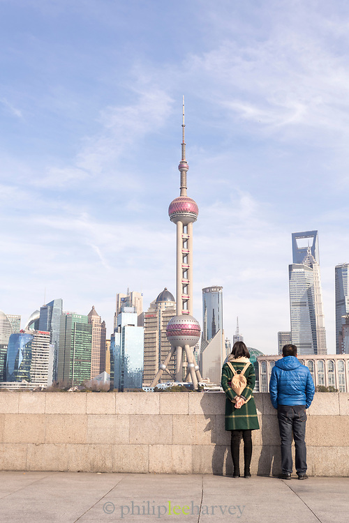 Tourists looking at the futuristic cityscape of Lujiazui skyline from the Bund, Shanghai, China