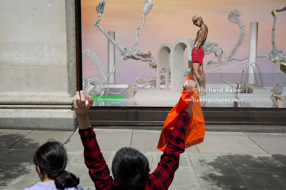 A boy stretches his arms while holding a plastic carrier bag opposite an ad for mens' underwear outside the London location of the Selfridges Department store on Oxford Street, on 2nd July 2019, in London, England.