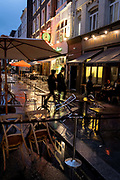 On a rainy night in Soho, tables set up for social distancing outside Bar Italia on Frith Street remain vacant at a time when recently re-opened bars and restaurants are desperate for customer business during the coronavirus pandemic, on 27th August 2020, in London, England.