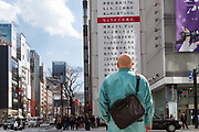 A man looks at a  large billboard on the side of the Sony Building in Ginza marking the sixth anniversary of the March 11th 2011 earthquake and tsunami in Tohoku. Ginza, Tokyo, Japan. Friday March 10th 2017 The billboard was created by Yahoo and shows the asks passers by to remember the disaster and the nearly 16,000 people who died. the line marked in red shows the maximum height of the tsunami (16.7 metres at Ofunato in Miyagi prefecture. The billboard is on display until March 12th.