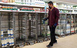 © Licensed to London News Pictures. 21/09/2021. London, UK. A staff member wearing a face covering walks past empty shelves of fresh milk, just after 8am this morning in Sainsbury's, north London, Fears of food shortages grow after two of the UK's biggest Carbon Dioxide (CO2) producers halted production last week due to soaring gas prices. UK food producers and supermarkets are warning that shoppers are likely to face food shortage caused by a lack of gas could hit this week. Photo credit: Dinendra Haria/LNP