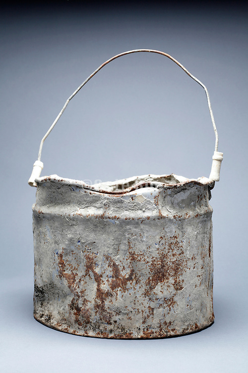 old rusty beaten up metal paint bucket that is intensive reused for cement work